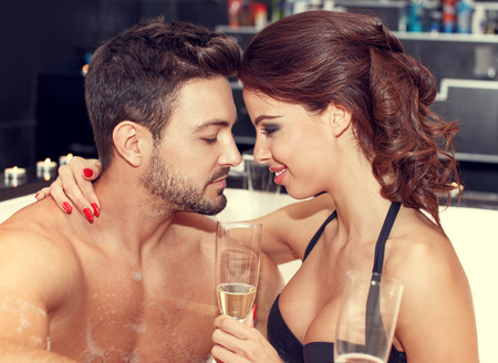 parejas romanticas: Pareja joven disfrutar de la luna de miel en el jacuzzi con champán