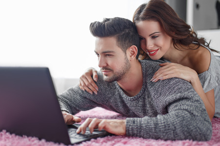 prone: Young couple with laptop lying prone on carpet, wi-fi technology Stock Photo