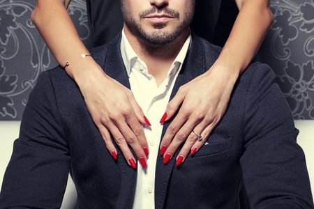 赤色の爪とセクシーな女性の手を受け入れる豊かな人間