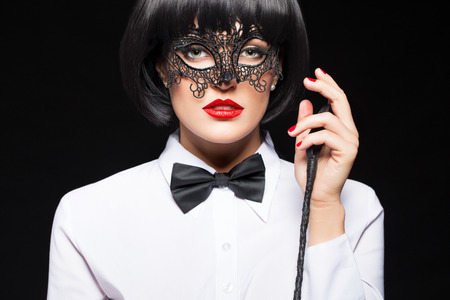 Sexy woman in wig posing with whip on black background, sensuality and punishment