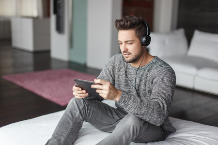 Young fashionable man listening music on tablet indoor by earphones Stock Photo
