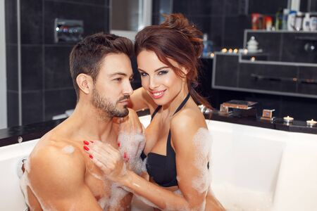 Happy young couple in jacuzzi, honeymoon