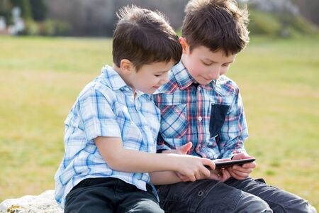 boys playing: Little boys playing on tablet, or messaging, wireless technology, outdoor Stock Photo