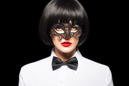 erotic fantasy: Sexy woman in wig and mask isolated on black