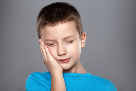Closeup portrait of young boy with tooth ache. Problem about from oral pain, touching face with hand, grey background. Negative emotion facial expression feeling