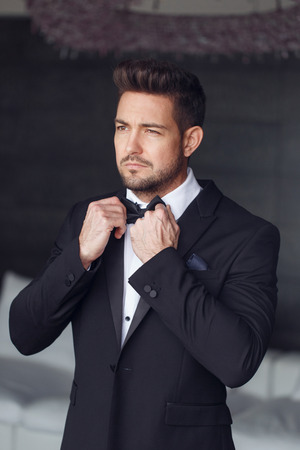 Sexy man dressing tuxedo and suit in luxury flat