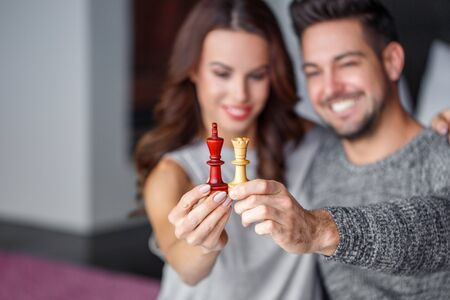 dating strategy: Happy couple date at home with chess figures, black king, white queen