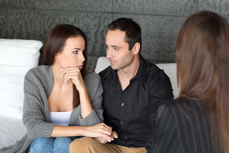 Young couple with a problem to consult a psychologist, therapy, holding each other hand