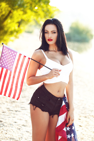 tits: Sexy young brunette woman with big tits and little USA flag, outdoor
