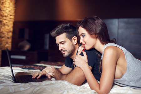 laptop home: Young couple online shopping from bedroom, lying on bed Stock Photo