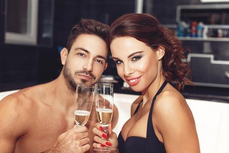 salud sexual: Pareja feliz con copas de champán en el jacuzzi, luna de miel