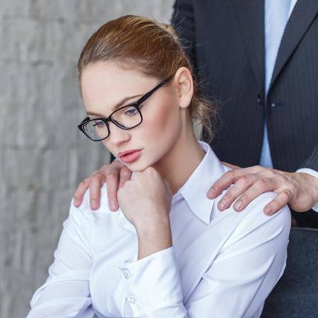 Boss put hands on secretary shoulder in office Foto de archivo