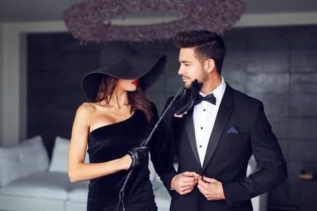 黒い帽子と若いマッチョな恋人たちのあごを保持している鞭の官能的な熟女女性