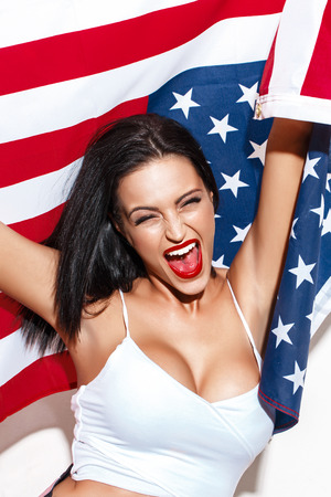 bawl: Happy woman shout with USA flag at white wall, open mouth, closed eyes