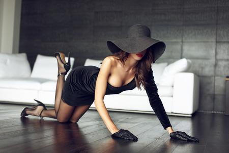 Sexy woman in black hat posing on the floor in luxury flat, sensuality Foto de archivo