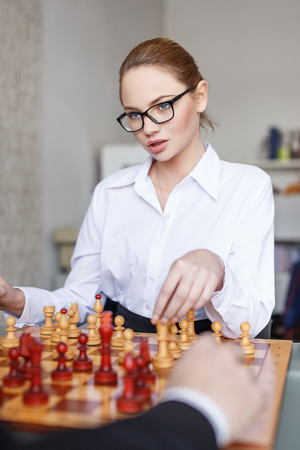 Sexy ceo playing chess with business partner in office