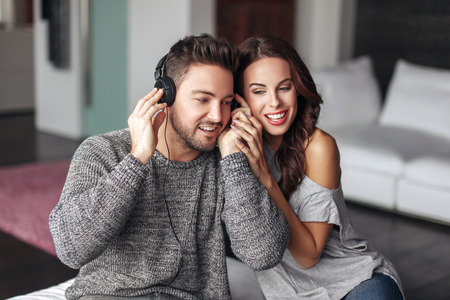woman listening to music: Happy young couple listening music and at home, sharing headphones