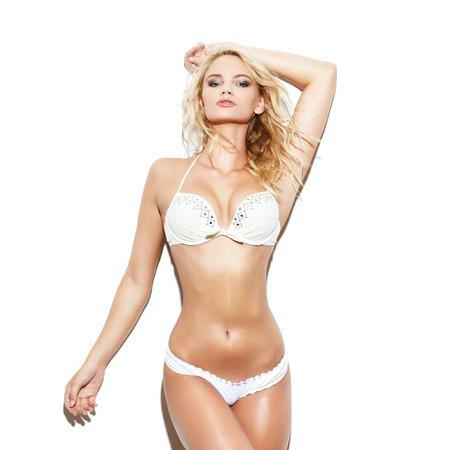 Sexy blonde kaukasische Frau im Bikini auf weiße Wand aufwirft Standard-Bild - 58340148