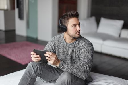 auriculares: Joven caucásico hombre atrapado música que escucha en la tablilla cubierta