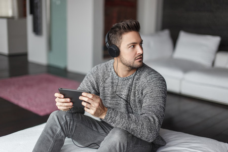 guys: Young caucasian man caught listening music on tablet indoor Stock Photo