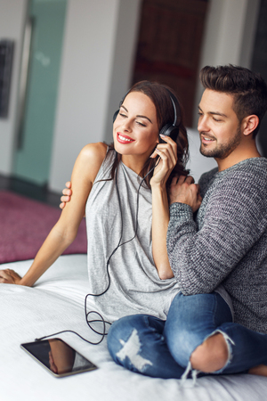 embracing couple: Young couple listening music on tablet by headphones indoors Stock Photo