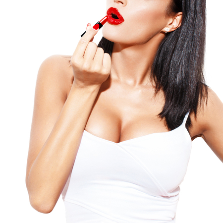 tits: Sexy woman with big tits apply red lipstick, isolated on white