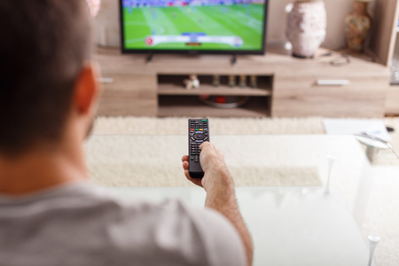 watching football: Man with remote control watching football match at home