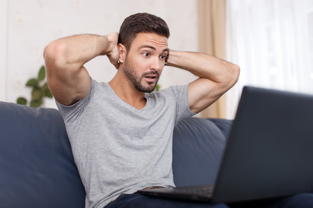 trouble: Man read bad news on laptop, big eyes, frightened expression
