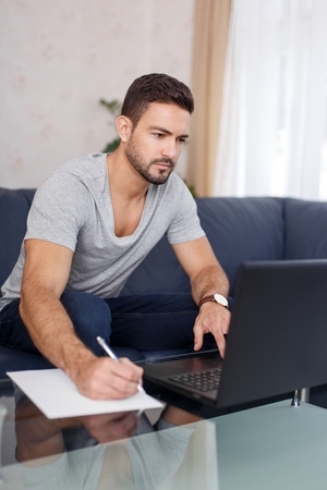 take a note: Casual man take a note from online document, using laptop, online communication Stock Photo