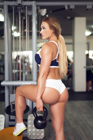 WOMAN FITNESS: Sexy woman with kettlebell workout in gym, listening music Stock Photo