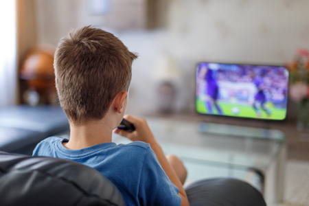 Excited little kid watching soccer match in TV at home Standard-Bild