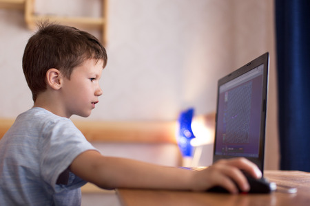 dependent: Little dependent boy playing game on laptop at home