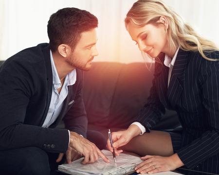 romance: Młody menedżer flirtuje z businesswoman w zachodzie słońca, umowy przeglądu, we wnętrzach