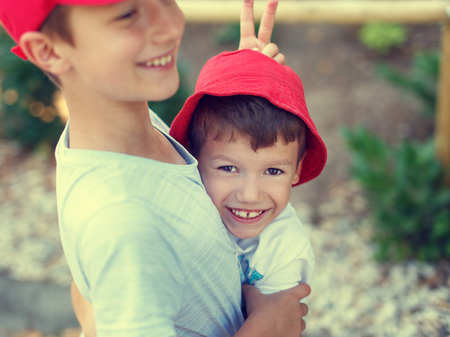 brothers: Happy carefree little boy showing donkey ear to younger brother, outdoor, summer holiday