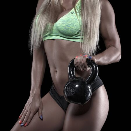 big breast woman: Strong bodybuilder woman doing biceps exercise with kettlebell, isolated on black