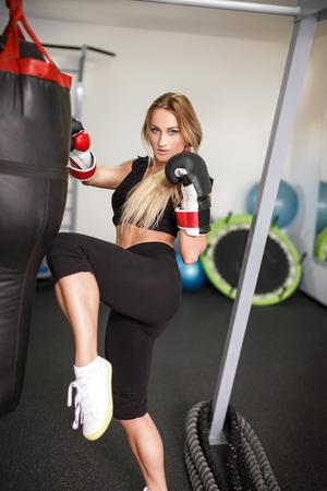 patada: kickboxer mujer perforación en la bolsa pesada en el gimnasio Foto de archivo