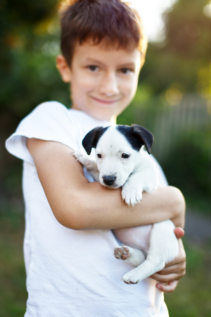 pet therapy: Happy little boy holding jack russell terrier kid outdoor