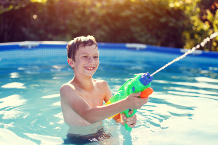 squirt: Happy little boy laugh and shoot with squirt gun in sunset Stock Photo