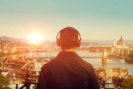 listening device: Young man listening music in sunset back view, Budapest, Hungary
