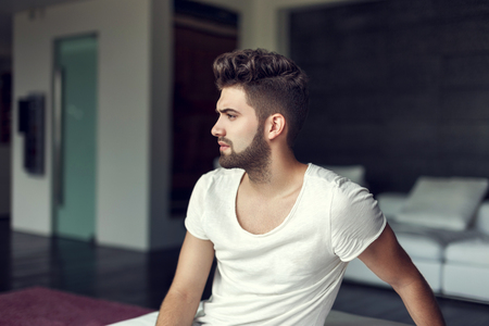 Young bearded hipster guy indoor, side view