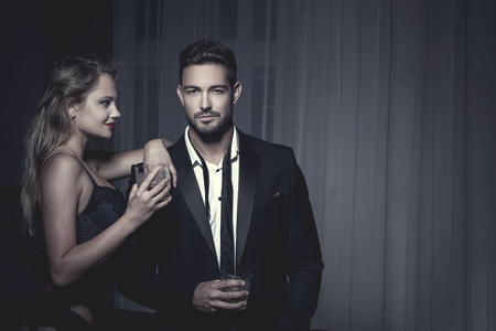 Rich macho young man drink whiskey with blonde lover at night, james bond Stock Photo