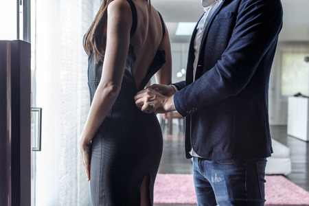 Macho man dressing woman into cocktail dress indoor, closeup