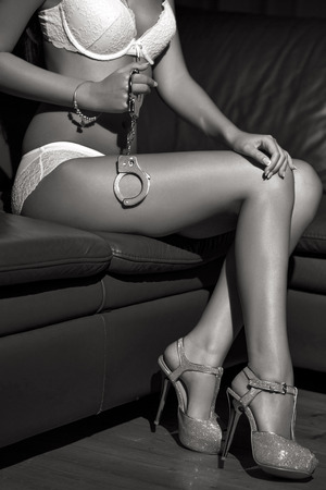 mujer desnuda sentada: Cuerpo de mujer sexy en ropa interior se sienta en el sofá con las esposas, BDSM, blanco y negro