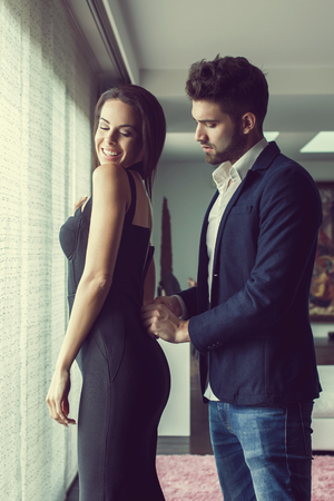dressing up: Stylish young man helps woman dressing up indoors