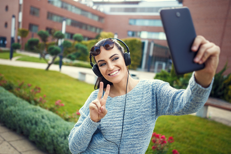 taking video: Young university student taking selfie with tablet, online video chat, listening music by headphones in park