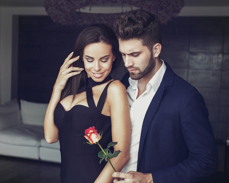 romantic man: Sexy young romantic man gives rose to stylish woman in luxury hotel room