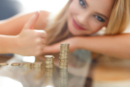 money and saving: Successful blonde woman thumb up at growing euro columns, indoor closeup portrait, depth of field, saving money concept