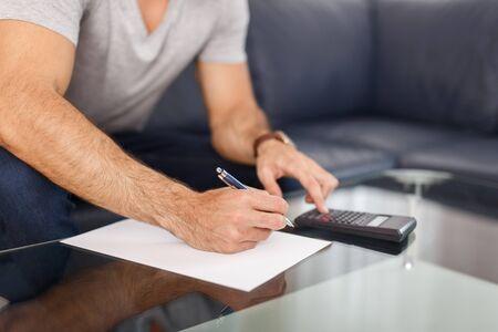 Man hands doing calculation on blank paper, closeup