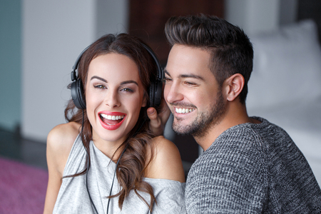 earphone: Young couple listening music by headphones indoor, laughing