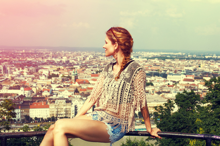 sightsee: Young woman sit on railing enjoying panorama of Budapest, sightsee, Hungary, vintage style, side view Stock Photo